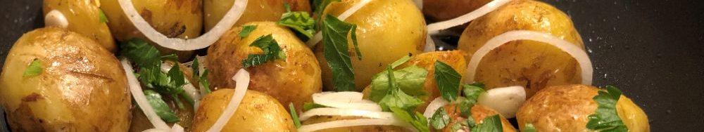Молода картопля з часником відварена і смажена на  сковороді.